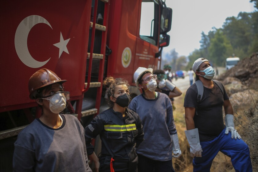 Turkish volunteers prepare to fight wildfires in Turgut village, near tourist resort of Marmaris, Mugla, Turkey, Wednesday, Aug. 4, 2021. Hundreds of volunteers have joined efforts to contain blazes that have swept through forests in Turkey's southern and southwestern coasts, fueled by a summer heatwave, low humidity and strong winds. The fires, described as Turkey's worst in living memory, have so far killed eight people _ including a teenaged volunteer who was carrying drinking water and other refreshments to firefighters in Marmaris. (AP Photo/Emre Tazegul)