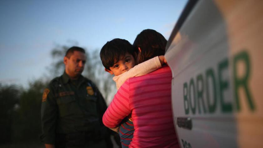 Una madre y su hijo responde a las autoridades migratorias en un punto fronterizo.