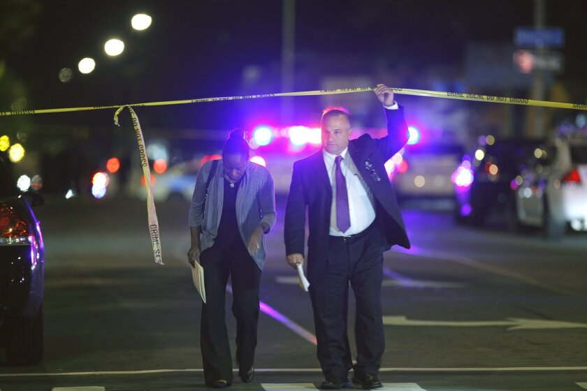 Police investigate the scene of a shooting Officer shot on Hudson Avenue in Rochester, N.Y. on Wednesday, Sept. 3 2014. Rural/Metro Medical Services say an officer was shot and taken to Rochester General Hospital, where he died. At least two other people were wounded in the shooting Wednesday night. Their conditions were not immediately known. The officer is the first member of the Rochester Police Department to be killed in the line of duty since 1959. (AP Photo/Democrat & Chronicle, Carlos Ortiz) MAGS OUT; NO SALES