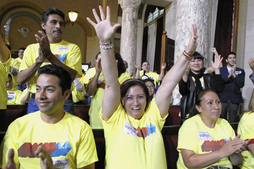 Blanca Aldana raises her hands in victory after the Los Angeles City Council approved a $15.37-per-hour minimum wage for workers at big hotels. The measure will be put to a second procedural vote next week.