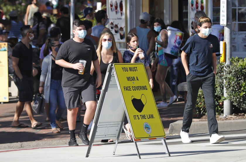 A mask-wearing group crosses the street as they walk along the sidewalks in Laguna Beach on Aug. 31.