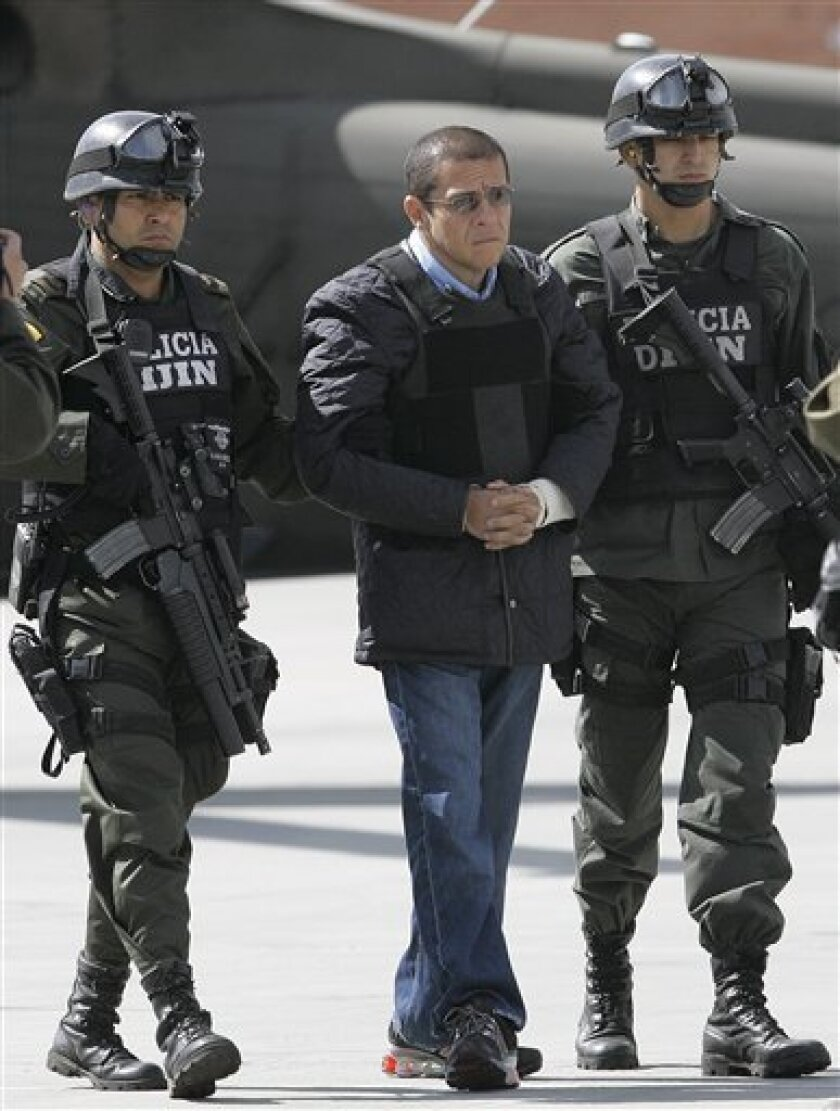 """Police officers escort Diego Montoya, center, known as """"Don Diego"""" before being extradited to U.S. at a military airport in Bogota, Friday, Dec. 12, 2008. Montoya is charged in two U.S. courts with drug trafficking, money laundering and murder. Colombian authorities say he sent tons of cocaine to the United States and is responsible for at least 1,500 killing in a two-decade career. (AP Photo/Fernado Vergara)"""