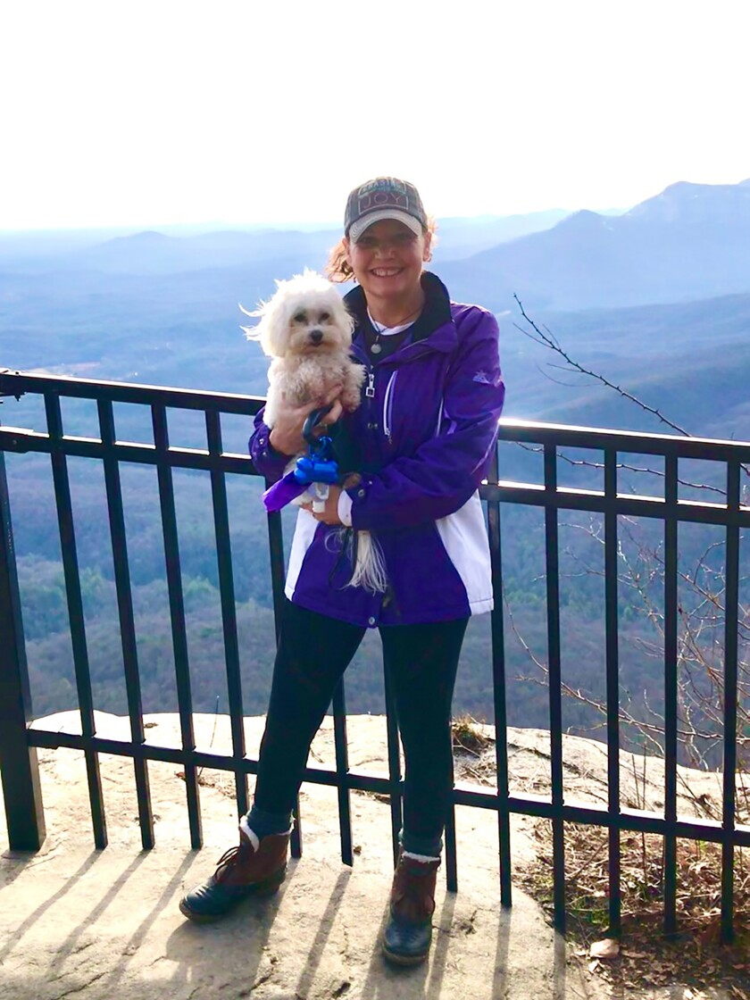 A woman holds a small white dog and poses for a photo in front of a mountain landscape.
