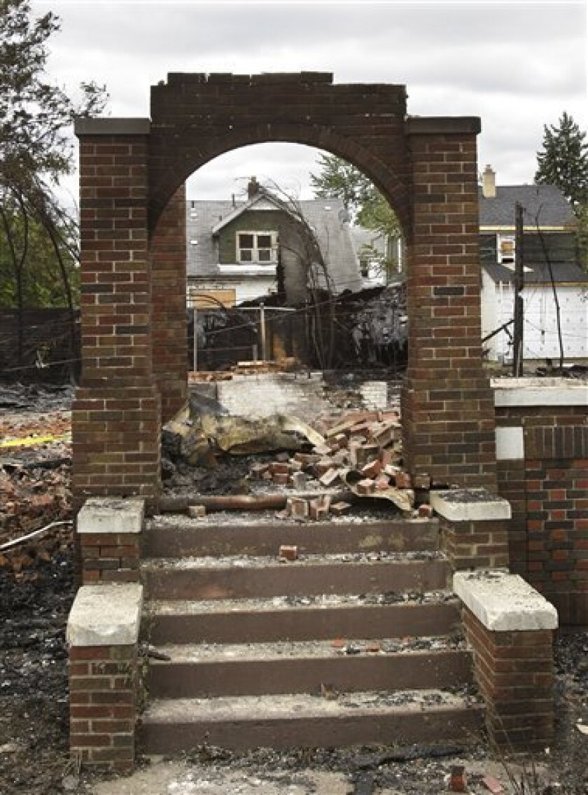 A burned home is seen through a remaining entryway of another home on Detroit's east side, Wednesday, Sept. 8, 2010. Wind-whipped flames swept through at least three Detroit neighborhoods, destroying dozens of homes, including many that were vacant, officials said. (AP Photo/Carlos Osorio)