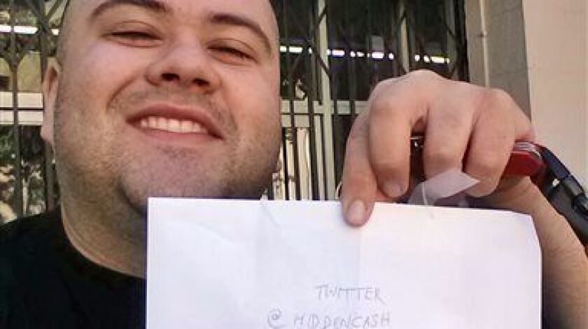 Sergio Loza holds up an envelope that had cash hidden in it in San Francisco, on Sunday, May 25, 2014.