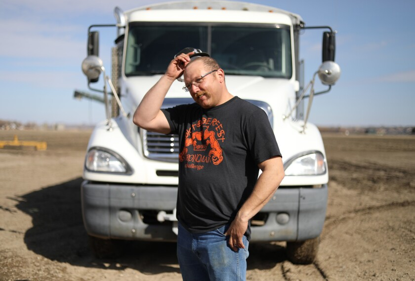 Cancer survivor Charley Butler with a truck he drives at times during the sugar beet harvest in Sidney, Montana
