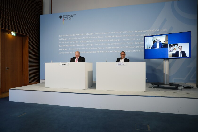 German Economy Minister Peter Altmaier, left, state secretary at the economic ministry Ulrich Nussbaum, right, attend a news conference with investor Dietmar Hopp, on the screen left, and CureVac CEO Franz-Werner Haas, on the screen right, at the economy ministry about the in Berlin, Monday, June 15, 2020. The German government is taking a 23 percent stake in the German company working on a potential vaccine for the coronavirus. (AP Photo/Markus Schreiber, Pool)