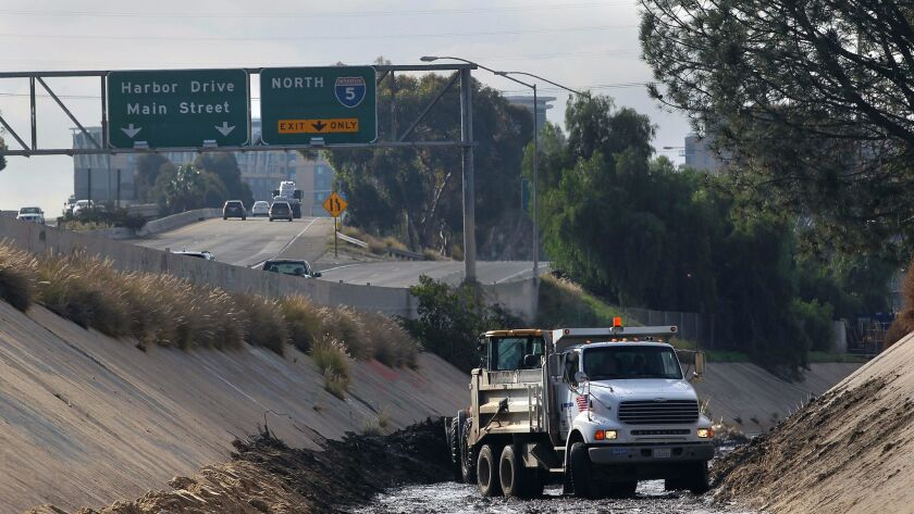 Workers using 10-wheel trucks and heavy equipment in 2016 between Interstate 5 and Interstate 15 where Chollas Creek is lined with concrete.| John Gastaldo / San Diego Union-Tribune