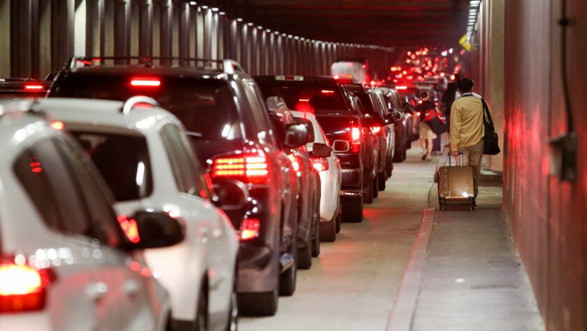Traffic backs up through the Sepulveda Boulevard tunnel as travelers pull their luggage toward LAX, where false reports of a gunman grounded flights and caused mass panic.