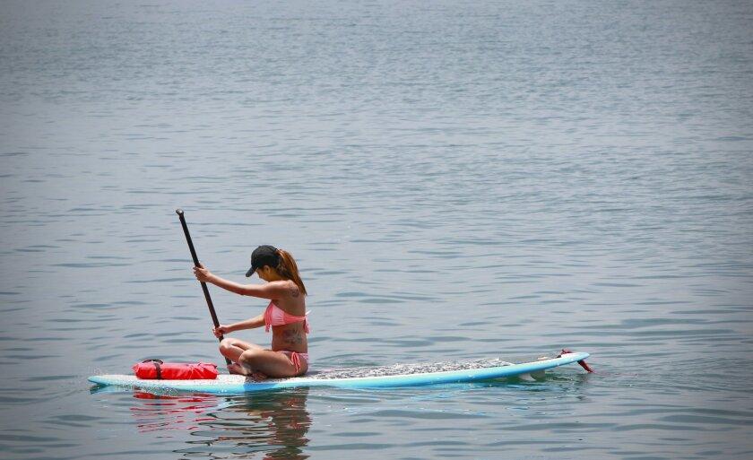 A visitor paddles her surfboard in Oceanside Harbor.