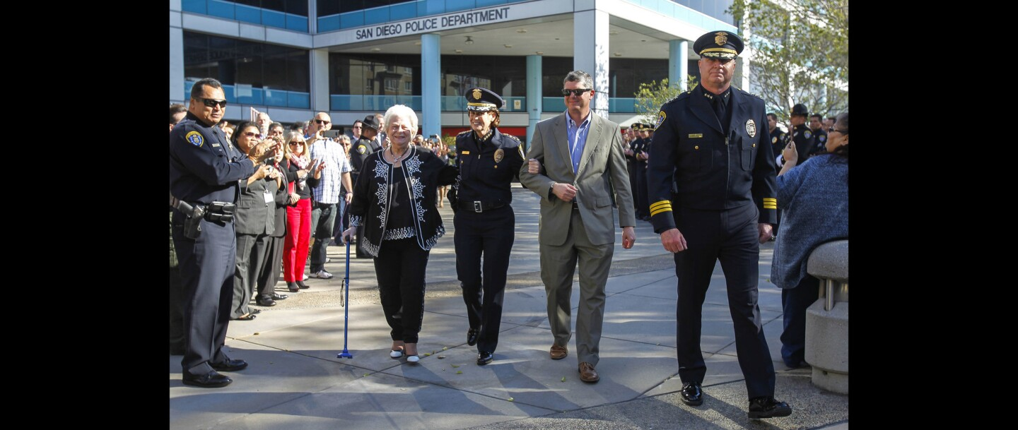 With Assistant Chief of Police Todd Jarvis leading them out, outgoing San Diego Police Chief Shelley Zimmerman walks arm and arm with her mother Elaine Zimmerman and brother Robert Zimmerman.