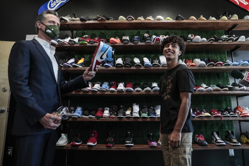 Gov. Gavin Newsom holds a sneaker while touring a shoe store