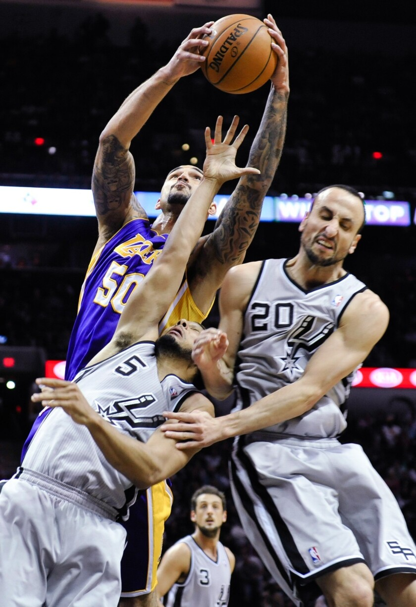 Lakers center Robert Sacre goes above Spurs guard Cory Joseph (5) and Manu Ginobili for a rebound in the second half.