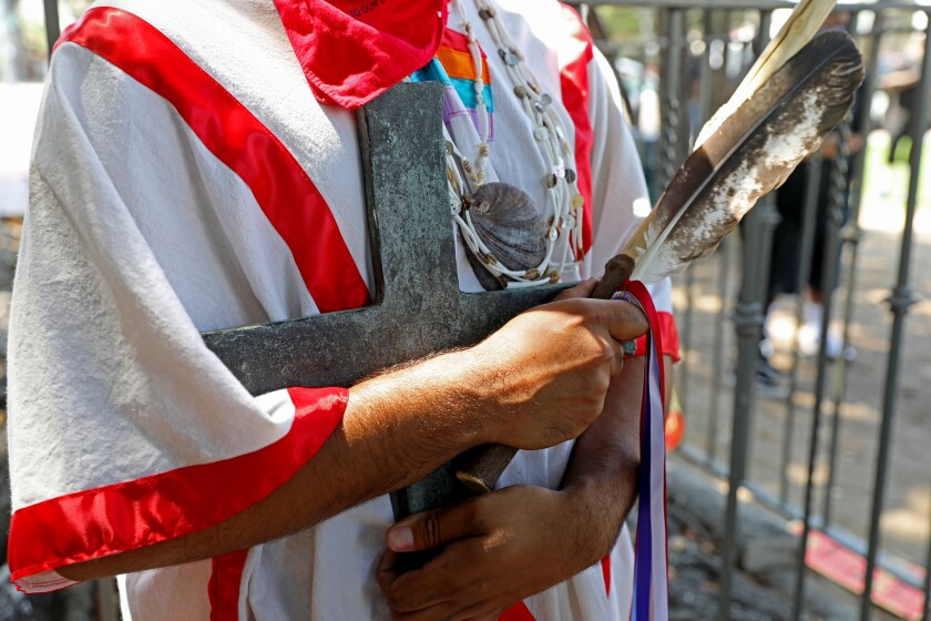 An activist in indigenous clothing holds the cross once held by the statue of Father Junipero Serra