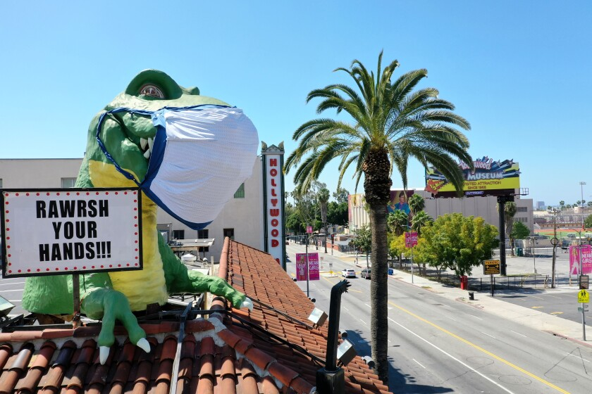 A giant T-Rex wearing a protective mask sends a Coronavirus message to a mostly empty intersection of Hollywood Blvd. and Highland Ave. from the top of Ripley's Believe It or Not! Odditorium, which is temporarily closed, in Hollywood, CA, on April 21, 2020.