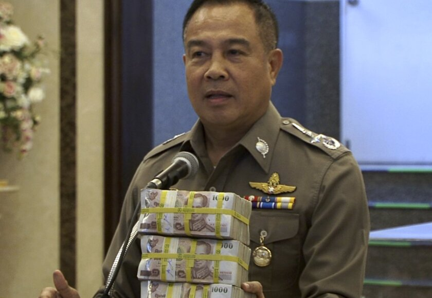 In this image taken from video, National police chief Somyot Poompanmoung holds a cash reward at a press conference in Bangkok, Thailand, Monday, Aug. 31, 2015. Thai police have awarded themselves a 3 million baht ($84,000) reward offered to the public for tips leading to the arrest of suspects in Bangkok's deadly bombing after a man was arrested over the weekend in an apartment where police found bomb-making equipment. (AP Photo/AP Video)