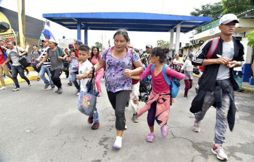 Miles de migrantes hondureños logran librar la valla que une la frontera con Guatemala para ingresar a México hoy, viernes 19 de octubre de 2018, en el margen del Río Suchiate (México). EFE