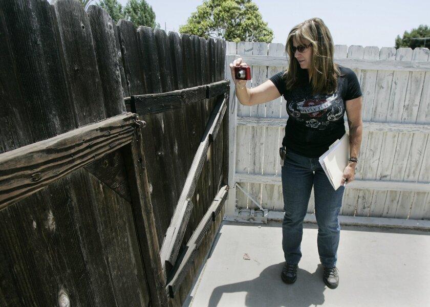 Sandi Stephens, Chula Vista's code enforcement officer, photographed an unlocked gate at a bank-owned home last week. (Eduardo Contreras / Union-Tribune)
