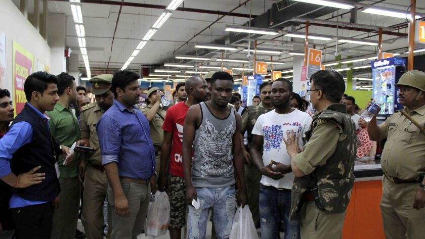 This photo taken on March 27, 2017 shows Indian police and onlookers surrounding African nationals a