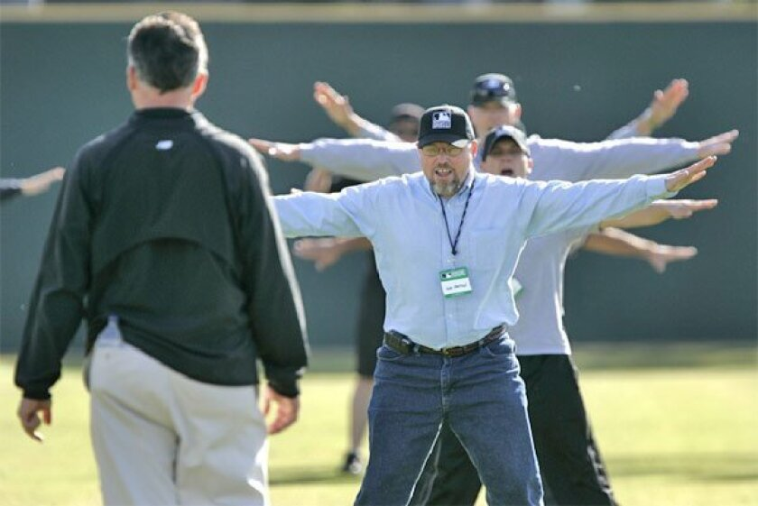 """""""He's safe!"""":  Camp director Rich Rieker (left) instructed his military group on the basics of umpiring at San Diego State University."""