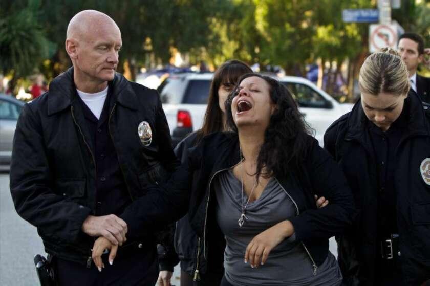 Una mujer que conocía a Reginald Doucet Jr., llora mientras la policía la escolta.