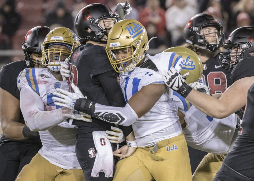 UCLA's Osa Odighizuwa (left) and Keisean Lucier-South hit Stanford quarterback Jack West.