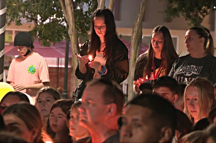 Hundreds gather for a candlelight vigil outside the Corona movie theater where two people were shot July 26.