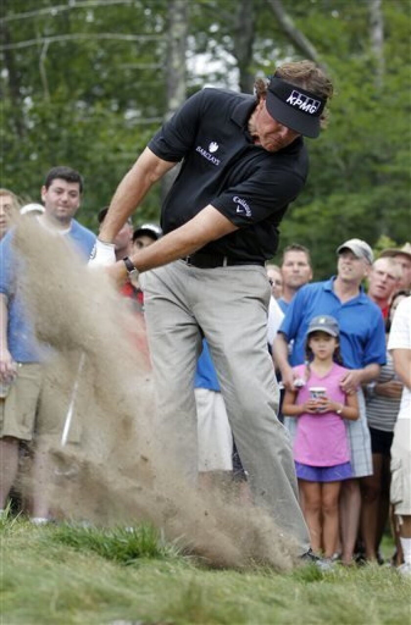 Phil Mickelson hits out of the rough on the 12th hole during the second round of the Deutsche Bank Championship golf tournament in Norton, Mass., Saturday, Aug. 31, 2013. (AP Photo/Stew Milne)