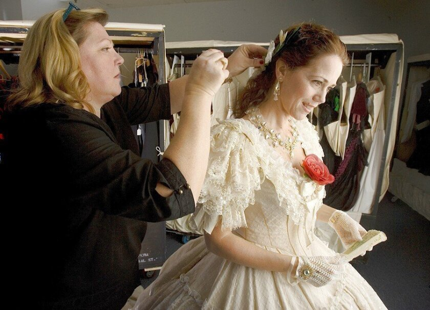 """The work is intricate as Tara Richards (left), a draper and cutter for the San Diego Opera, adjusts Elizabeth Futral's costume during a fitting for """"La Traviata."""""""