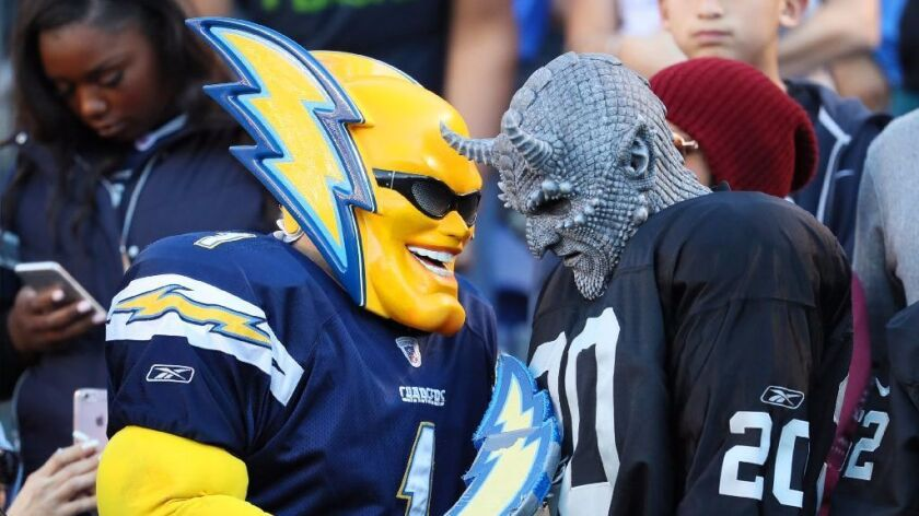 San Diego Chargers and Oakland Raiders fans play the part at Qualcomm Stadium on Dec. 18, 2016.