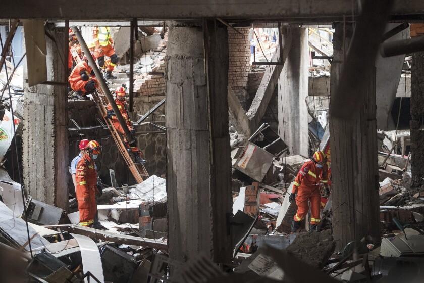 En esta fotografía publicada por la agencia noticiosa Xinhua, rescatistas buscan sobrevivientes el domingo 13 de junio de 2021 entre los escombros provocados por una explosión de gas en la ciudad de Shiyan, en la provincia central de Hubei, China. (Xiao Yijiu/Xinhua vía AP)