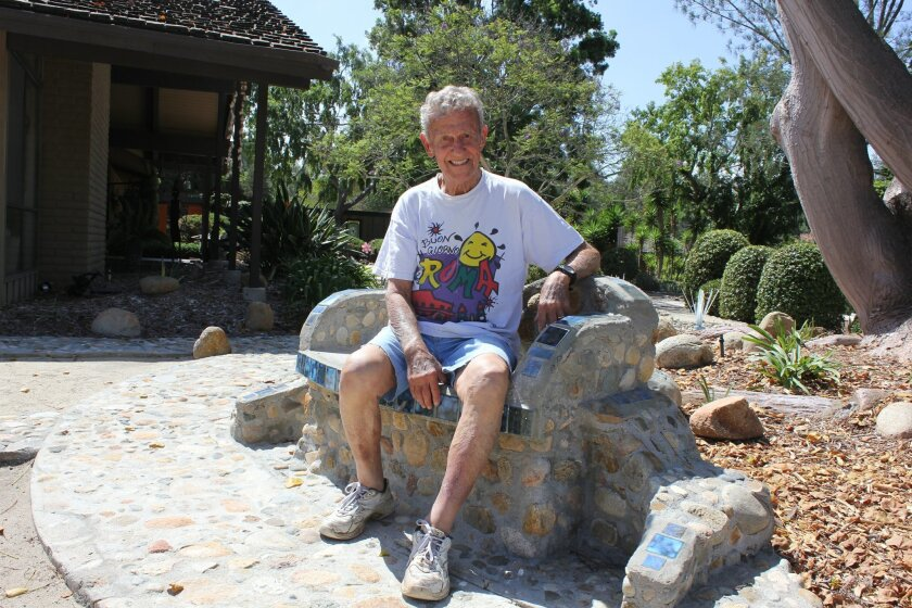 "Chuck Bahde sits on one of the ""love seats"" he built in his drought-resistant garden. Photo by Joe Tash"