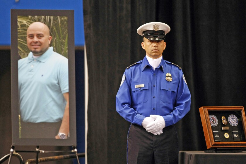 A Transportation Security Administration officer stands in front of a portrait of slain TSA officer Gerardo Hernandez during his public memorial after he was shot during a 2013 rampage by Paul Ciancia. Three others were wounded before Ciancia was shot by police.