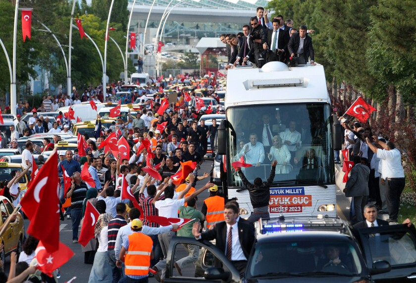 """Turkish Prime Minister Recep Tayyip Erdogan (at left in bus) and his wife Emine wave to supporters on their arrival in Ankara on Sunday. Erdogan warned today that the patience of his Islamic-rooted government """"has a limit"""" as mass protests against his decade-long rule raged for a 10th day."""