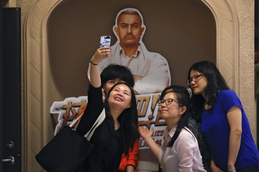 In this Monday, May 22, 2017 photo, a group of Chinese women take a selfie with a poster of Indian B