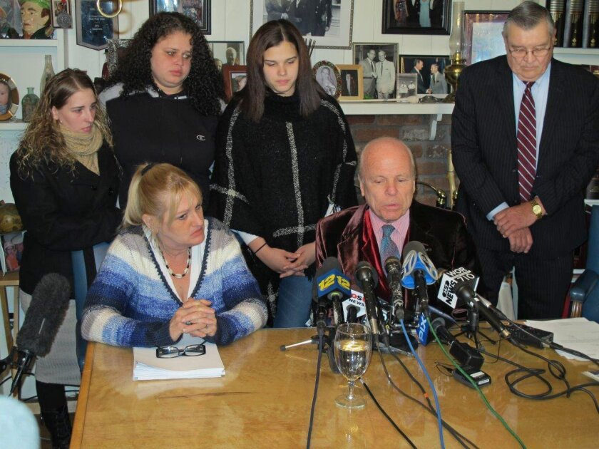 Attorney John Ray, seated, speaks at a press conference at his office in Miller Place, N.Y., on Friday, Feb. 12, 2016. Ray represents the family of Shannan Gilbert, a Jersey City, N.J., prostitute whose remains were found near where police discovered the bodies of 10 other slain people in the notor