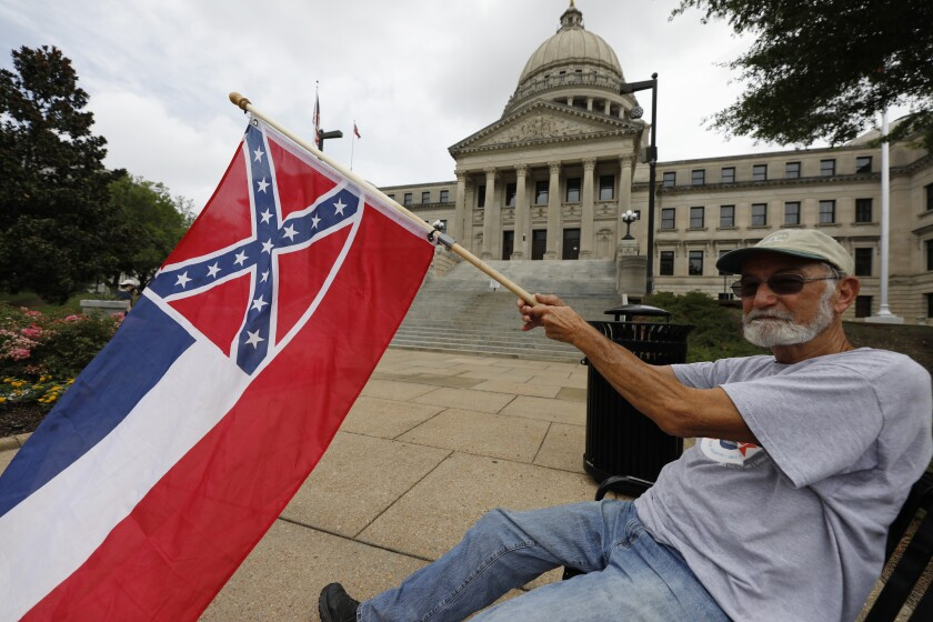 A man waves the current Mississippi state flag as he sits in front of the Capitol.
