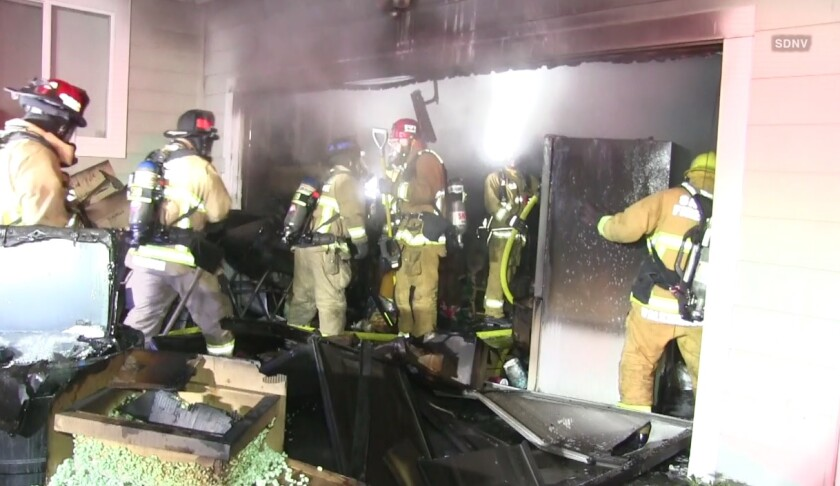 Santee firefighters work to clear out a garage where a fire broke out Thursday night.