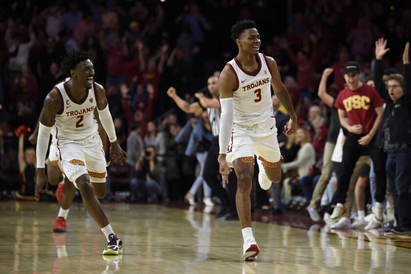 USC's Elijah Weaver, right, and Jonah Mathews celebrate after Weaver's three-pointer sent Saturday's game to overtime.