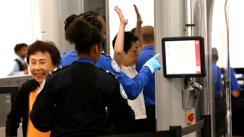Passengers arriving from international flights pass through an expedited Transportation Security Adm