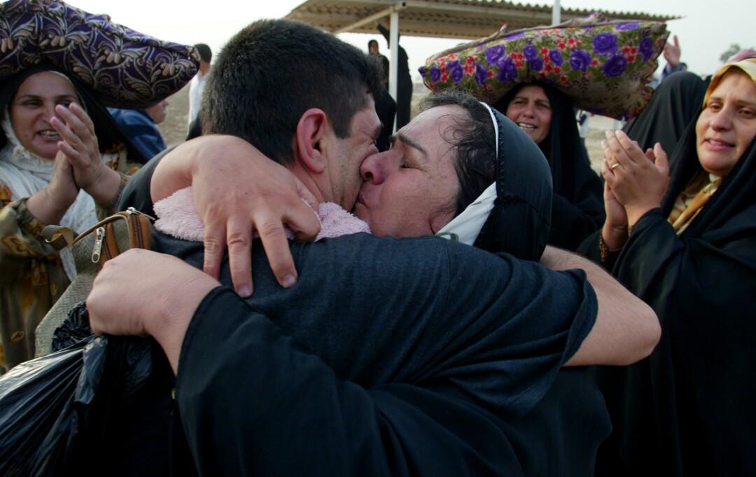 مردی مادرش را در آغوش می گیرد در حالی که سایر اطرافیان او دست می زنند