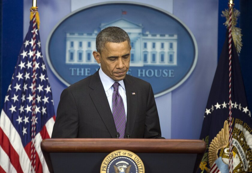 President Barack Obama arrives to the podium to speak in the briefing room of the White House in Washington, Thursday, Dec. 5, 2013, about the death of Nelson Mandela. Obama says the world has lost an influential, courageous and 'profoundly good' man with the death of anti-apartheid icon Mandela. (AP Photo/Carolyn Kaster)