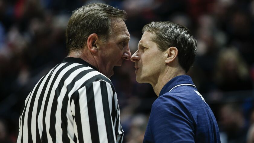Nevada coach Eric Musselman and official David Hall exchange words during the first half of SDSU's 65-57 win at Viejas Arena on Wednesday.