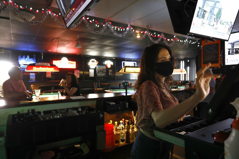Bartender MIriam Niemela works the register at the Carriage House bar in Kearny Mesa.