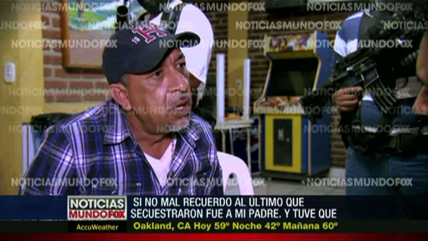 "In this image from a December 2013 video from Mundo Fox via APTN, Servando ""La Tuta"" Gomez Martinez, leader of the Knights Templar cartel, is interviewed while guarded by masked and armed men in Mexico's Michoacan state."