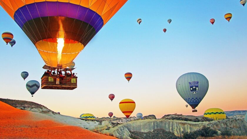 Up, up and away at sunrise in Cappadocia, where hot air balloons drift over a supernatural landscape