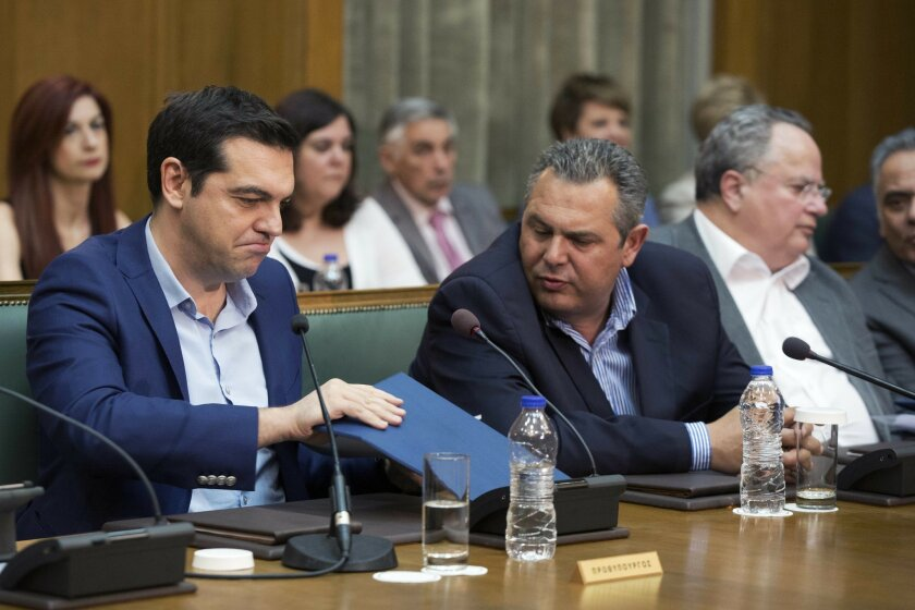 Greek PrIme minister Alexis Tsipras, left, and Greek Defense Minister and party leader of the Independent Greeks Panos Kamenos chat during a cabinet meeting on Thursday, June 2, 2016. Parliament approved a final round of austerity measures Thursday demanded by lenders for the release of further bai