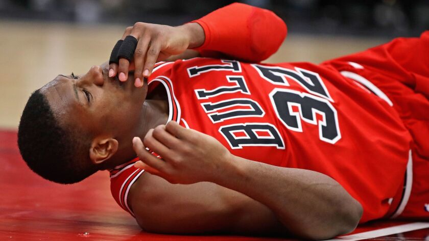 Chicago's Kris Dunn lies on the floor after suffering a mouth injury following a dunk against Golden State on Wednesday.