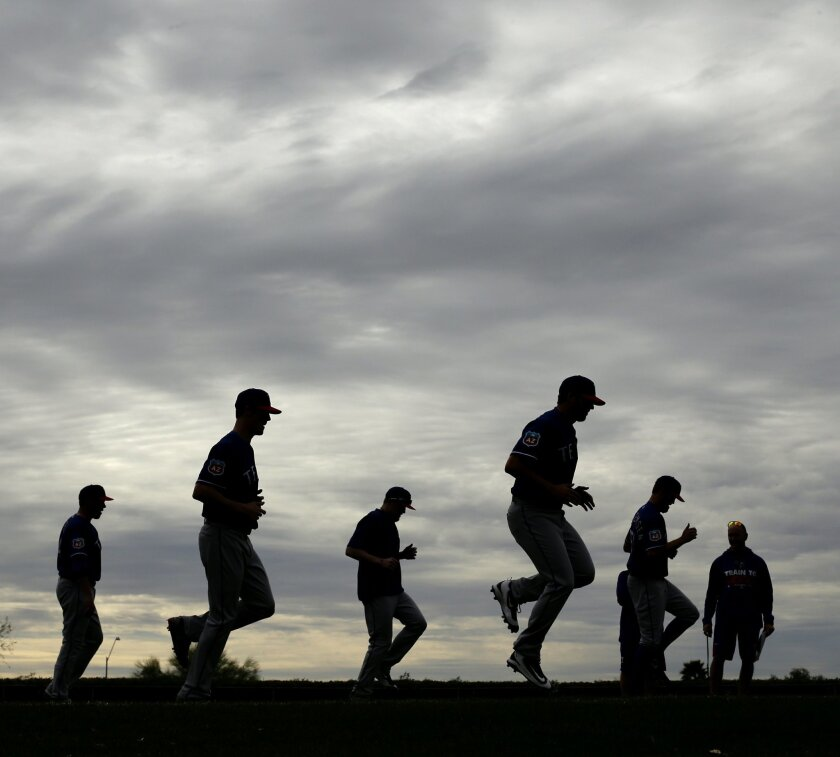 Texas Rangers players warm up before spring training baseball practice Friday, Feb. 19, 2016, in Surprise, Ariz. (AP Photo/Charlie Riedel)