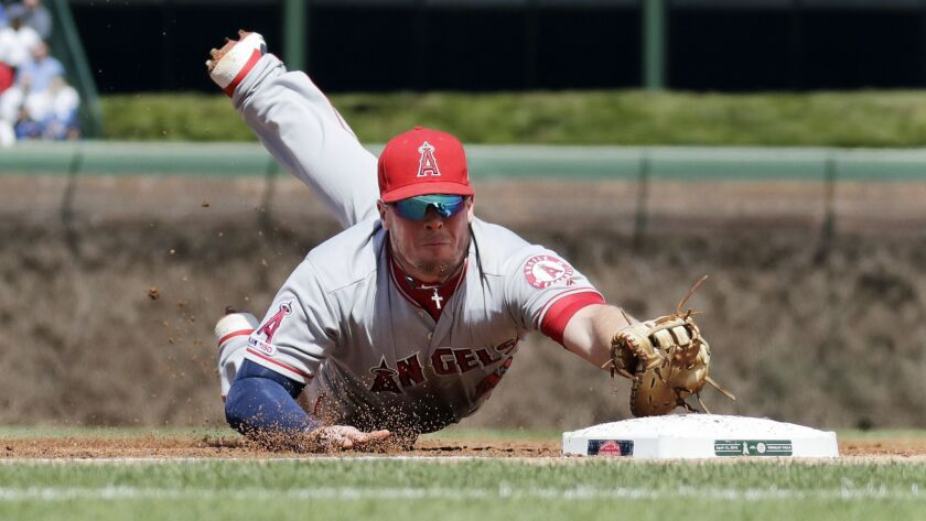 Angels first baseman Justin Bour dives to snag a groundball hit by the Chicago Cubs' Anthony Rizzo during the first inning.